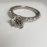 round cut solitaire engagement ring with diamond accented band