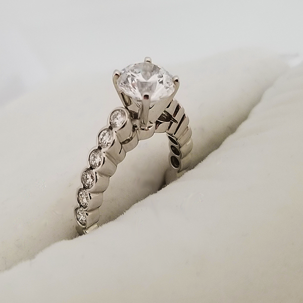 Round Solitaire with Bezel Set Diamond Accents on the Band