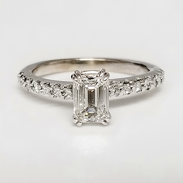 Emerald cut solitaire engagement ring with diamond accented band