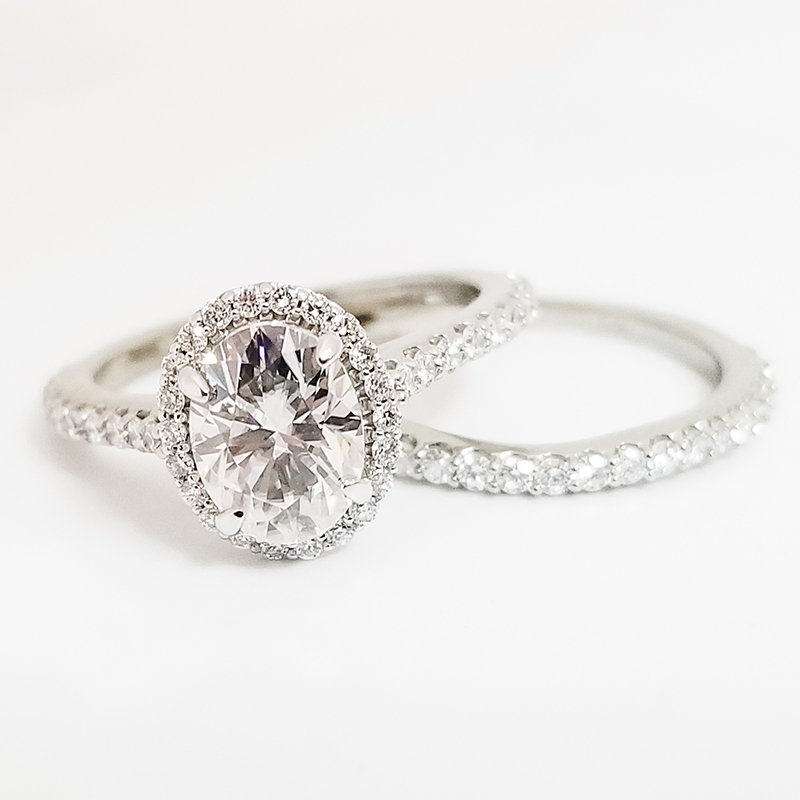 Oval halo engagement ring with diamond wedding band